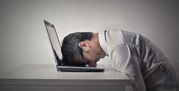 man sitting at a desk with his face on a laptop, clearly tired