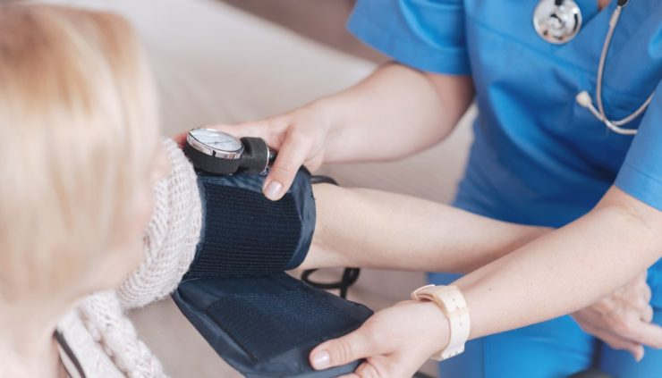 woman getting her blood pressure taken with a cuff by a nurse