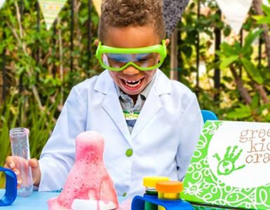 a little boy looks excited to play with Green Kid Craft box items