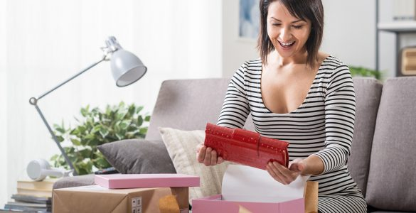 woman-in-dress-opens-package-in-living-room