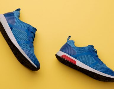 blue running shoes on a yellow background