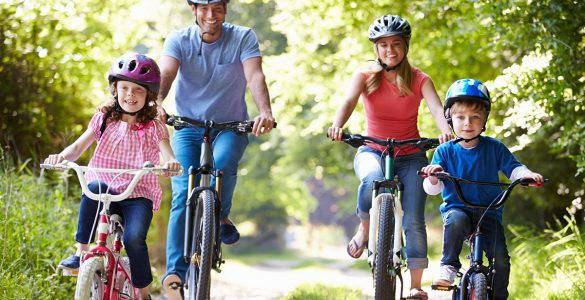 family-of-four-rides-bikes-on-sunny-day