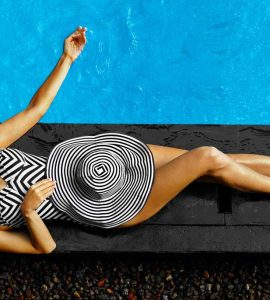 woman in a swimsuit with a sunhat next to a pool