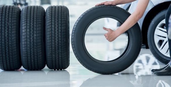 person-holds-car-tire-in-shop-and-gives-thumbs-up