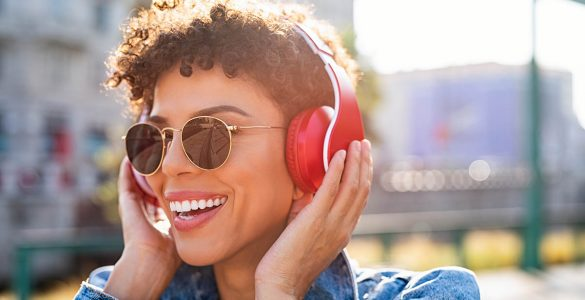 woman listens to music on headphones outside